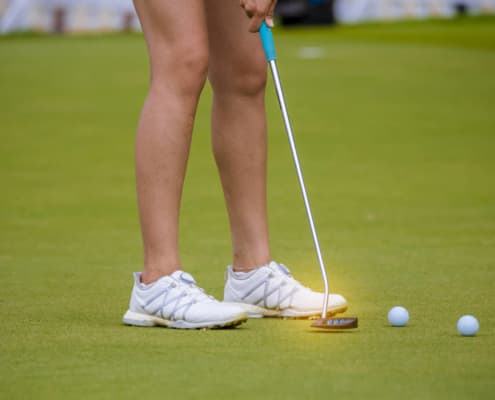 golfer pushing golf to hole on golf course